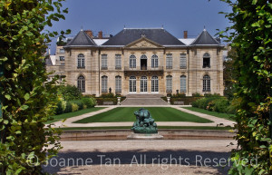 Symmetrical French building's back door, window, and balcony overlook a rectangular lawn surrounded with a walkway and hedges carefully manicured. Rodin's statue of Infernal's blind father's cannibalism with his rear.
